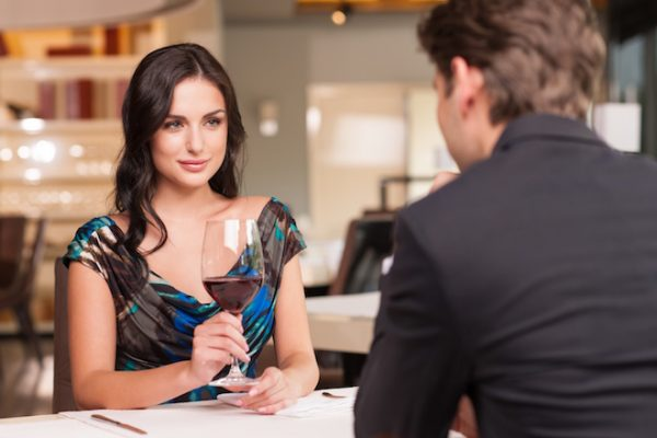 Seducing beautiful woman looking at her lover with wine glass. Having romantic talk